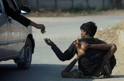 Pessoa afetada pela pólio pede esmolas em uma rua de Islamabad (Paquistão).