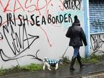 A woman walks her dog past past graffiti with the words 'No Irish Sea Border' in Belfast city centre, Northern Ireland, Wednesday, Feb. 3, 2021. Politicians from Britain, Northern Ireland and the European Union are meeting to defuse post-Brexit trade tensions that have shaken Northern Ireland's delicate political balance. British Cabinet minister Michael Gove, European Commission Vice President Maros Sefcovic and the leaders of Northern Ireland's Catholic-Protestant power-sharing government will hold a video conference to discuss problems that have erupted barely a month after the U.K. made an economic split from the 27-nation EU. (AP Photo/Peter Morrison)