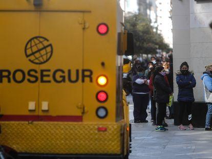 Fila de pessoas para entrar em um banco, em Buenos Aires.
