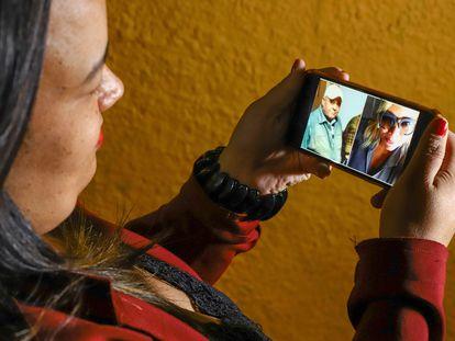 A recepcionista Maíra Diniz Câmpara segura celular com fotos do pai e da irmã, vítimas da covid-19