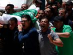 Mourners chant Islamic slogans while carrying the body of Awad Abu Selmiya, during a funeral of thirteen Hamas militants outside a mosque in Gaza City, Thursday, May 13, 2021.  Gaza residents are bracing for more devastation as militants fire one barrage of rockets after another and Israel carries out waves of  airstrikes. (AP Photo/Adel Hana)