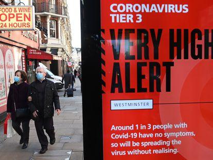 Pedestres passam diante de anúncio do Governo britânico sobre o coronavírus, hoje em Londres.