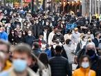 People wear the mandatory face masks in a shopping street in Dortmund, Germany, Monday, Nov. 23, 2020. Germany faces a partial lockdown due to the coronavirus pandemic, with restrictions at least until the end of November. (AP Photo/Martin Meissner)