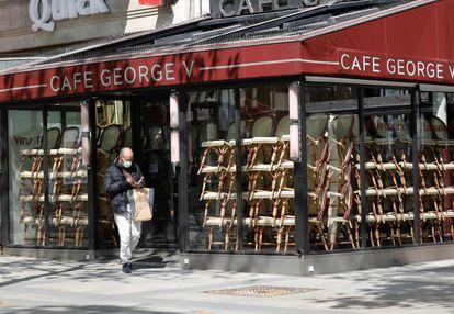 Um homem passa diante de um café fechado em Paris.