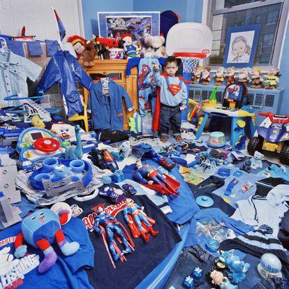 Menino mostra seus brinquedos azuis.