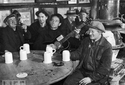 """Woody Guthrie se apresenta em um bar de Nova York, em 1943, com seu famoso violão onde se lê: """"Esta máquina mata fascistas""""."""