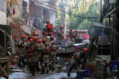 Bombeiros tentam resgatar outras pessoas presas aos escombros após desabamento de prédio de quatro andares no Rio.