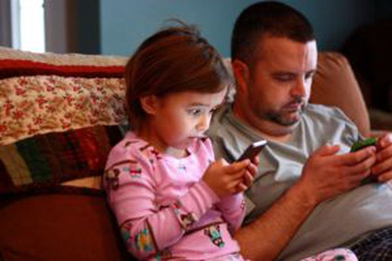 Uma menina e seu pai concentrados nos celulares.