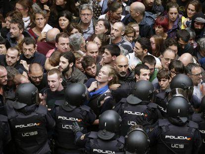 Agentes anti distúrbios da Polícia Nacional isolam catalães.