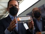 Brazil's Sao Paulo state governor, Joao Doria, and director of Instituto Butantan, Dimas Tadeu Covas, hold boxes of the China's Sinovac vaccine against the coronavirus disease (COVID-19) as a cargo plane containing the vaccines arrives at Sao Paulo International Airport in Guarulhos, Brazil November 19, 2020. REUTERS/Amanda Perobelli