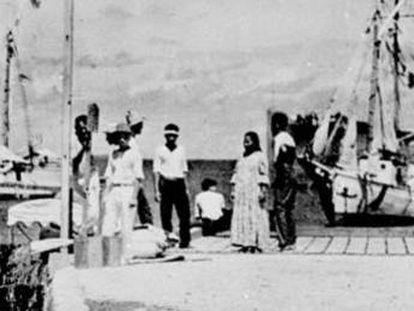 No centro do grupo no cais está a figura que o History Channel afirma que poderia ser Amelia Earhart. À esquerda, ao lado do poste, o suposto Noonan.
