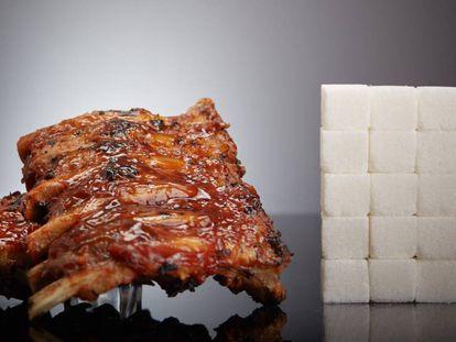 Costelas assadas com molho barbecue ao lado do açúcar que contêm, em torrões.