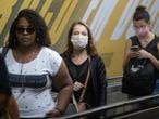 Commuters wear face masks as a precaution against the spread of the new coronavirus in a subway station in Sao Paulo, Brazil, Monday, March 16, 2020. According to the World Health Organization, most people recover in about two to six weeks from the new coronavirus, depending on the severity of the illness. (AP Photo/Andre Penner)