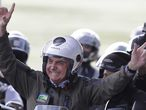 Brazil's President Jair Bolsoanro, waves to supports before a motorcycle rally with supporters representing the moto clubs in honor of Mother's Day, in Brasilia, Brazil, Sunday, May 9, 2021. (AP Photo/Eraldo Peres)