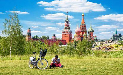 Ciclista urbano descansa no parque Zaryadye, em Moscou, com o Kremlin e a catedral de São Basílio ao fundo.