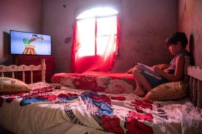 Danilo assiste a desenhos na TV antes de retomar os estudos com a ajuda da mãe.