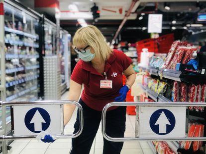 Funcionária desinfeta supermercado, em março de 2020.