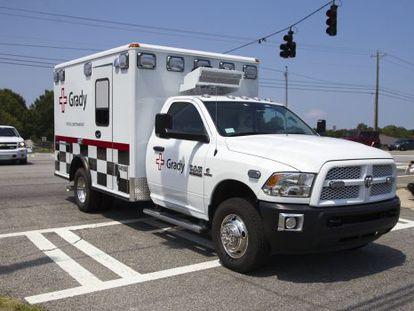 A ambulância que leva Nancy Writebol chega escoltada ao hospital da Universidade Emory.