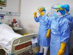Miembros del personal médico animando a un paciente infectado por el  coronavirus en una sala de aislamiento en un hospital en Zouping, en la provincia china de Shandong, el pasado martes.