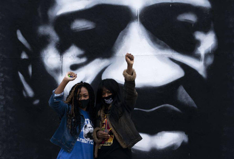 Duas mulheres em frente a um mural de George Floyd em Minneapolis, em outubro.
