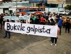 """People hold a banner reading """" Bukele coup plotter"""" as they protest against the removal of Supreme Court judges and the Attorney General by Salvadoran congress, in San Salvador, El Salvador, May 2, 2021. REUTERS/ Jose Cabezas"""