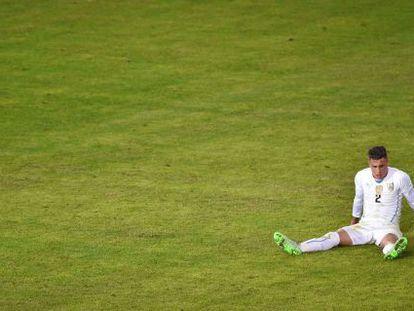 O zagueiro do Uruguai, José María Giménez, estirado em campo.