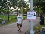 May 15, 2020 - Singapore, Republic of Singapore: A man at Bishan-Ang Mo Kio Park covers his face with a protective face mask and walks past a signpost on Covid-19 informing about compulsory measures to further reduce the spread of the coronavirus. With the exception of strenuous exercise activities like cycling or running everyone is required to wear a mask at all times when leaving home and being outside or in public places. (Olaf Schuelke/Contacto)   15/05/2020 ONLY FOR USE IN SPAIN