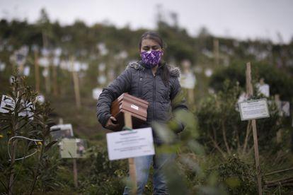 Uma mulher carrega uma urna com as cinzas de um parente, que morreu de complicações relacionadas à covid-19 na Reserva Natural El Pajonal de Cogua, ao norte de Bogotá, Colômbia.