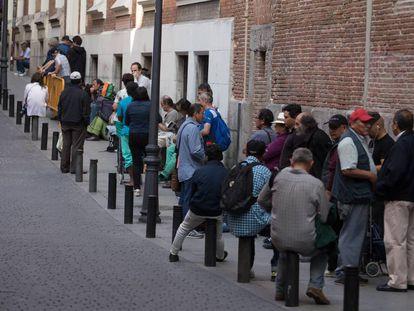 Um grupo de pessoas faz fila para entrar em um refeitório social em Madri