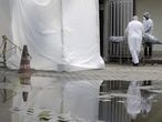 Healthcare workers wearing protective gear transport a body of a person to a refrigerated truck as they are seen reflected in a puddle during the coronavirus disease (COVID-19) outbreak, at the Lourenco Jorge hospital in Rio de Janeiro, Brazil May 8, 2020. REUTERS/Ricardo Moraes