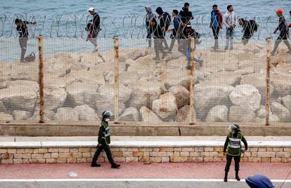 Agentes de segurança marroquinos montam guarda enquanto um grupo de emigrantes caminha pela costa na cidade nortista de Fnideq, em uma tentativa de cruzar a fronteira nesta terça-feira.