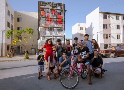 """Jovens da Vetinflix em frente ao mural que está sendo pintado em homenagem à paródia """"La Casa Duz Vetim""""."""