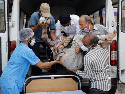 Paciente com problemas respiratórios dá entrada num hospital de Ahmedabad, nesta quarta-feira.