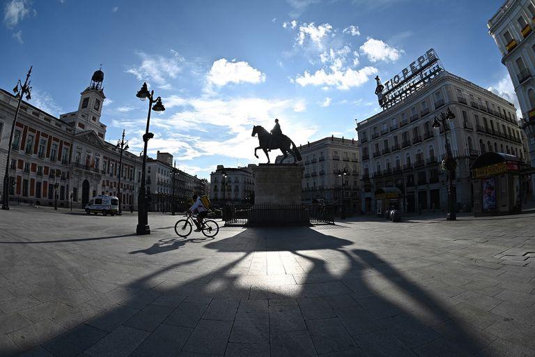 Entregador atravessa de bicicleta a habitualmente movimentada praça Puerta del Sol, no centro de Madri, no sábado passado.
