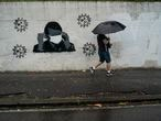 A man walks past a wall emblazoned with a mural depicting Brazil's President Jair Bolsonaro putting on a protective face mask amid the new coronavirus pandemic in Rio de Janeiro, Brazil, Thursday, July 30, 2020. (AP Photo/Leo Correa)