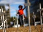 An activist from Black Coalition for Rights, which represents Brazilian Black movements, gestures as she stands near the crosses in tribute to the coronavirus disease (COVID-19) victims, in front of the National Congress after delivering a formal request of impeachment against Brazil's President Jair Bolsonaro, in Brasilia, Brazil August 12, 2020. REUTERS/Adriano Machado