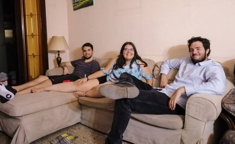 María Hernández na sala de sua casa, com seus dois colegas moradia.