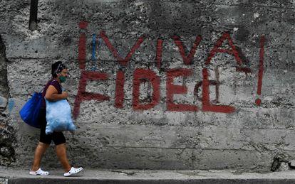 Mulher passa por pichação em que se lê Viva Fidel!, em Havana, neste 26 de julho.