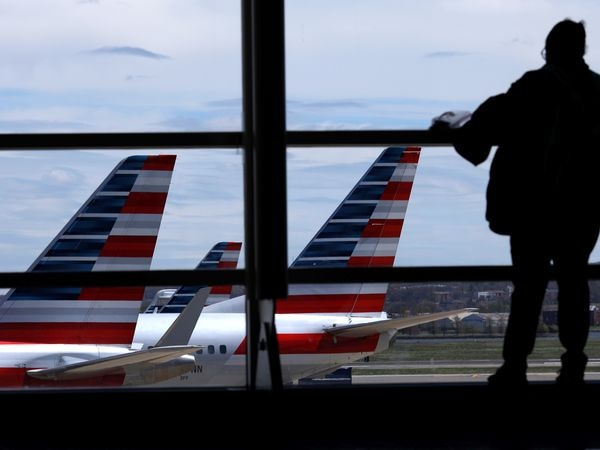 American Airlines  aircrafts are seen while a passenger waits for boarding at the Reagan International Airport as the spread of coronavirus disease (COVID-19) continues, in Washington, U.S., April 3, 2020. Picture taken April 3, 2020. REUTERS/Carlos Barria