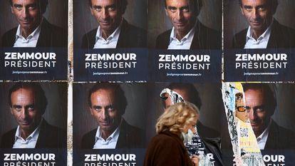 Uma mulher passa por cartazes do polemista Éric Zemmour em Paris, em 13 de outubro.