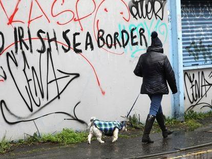 """Uma mulher passa diante de um muro de Belfast onde se lê: """"Sem fronteiras no mar da Irlanda"""", nesta quarta-feira."""