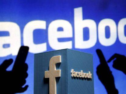 Dos personas usan sus móviles en frente del logo de Facebook.