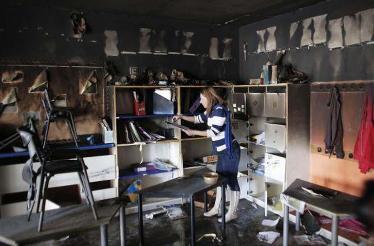 Uma trabalhadora limpa uma sala de aula da única escola mista árabe-judaica de Jerusalém, incendiada no sábado em um ataque que a polícia atribui a ultranacionalistas judeus.