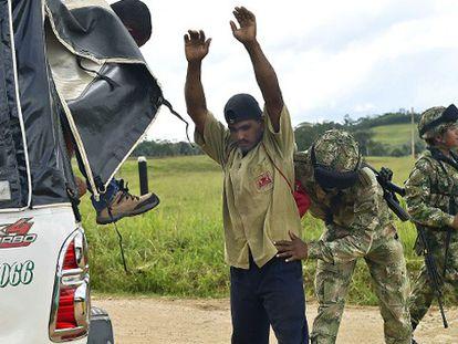Soldados colombianos revistam um camponês.
