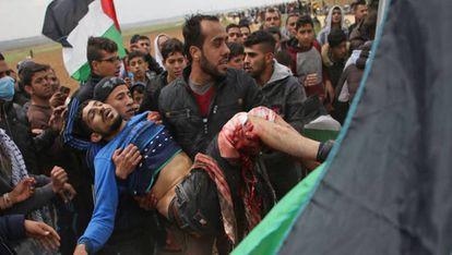 Um jovem palestino é socorrido após ter sido ferido durante uma manifestação perto da fronteira com Israel