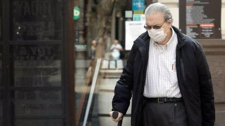 Una persona mayor protegida con mascarilla arrastra un carro frente a un comercio cerrado, en Valencia.