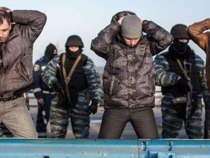 Forças pró-russas averiguam um grupo de homens na entrada da Crimeia, na segunda-feira.