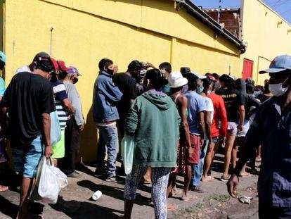 Dezenas de pessoas esperam nesta quarta-feira, dia 21 de julho, por uma doação de ossos de boi no açougue Atacadão da Carne, em Cuiabá (MT)