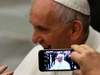 Uma pessoa tira uma foto do papa Francisco no Vaticano.