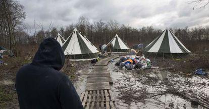 Um migrante caminha até um dos alojamentos do campo de Grande-Synthe (França).
